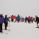 Skiers gather at the summit and try to decide which of the many runs to hit.